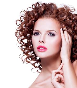 흰색 바탕에 손으로 그녀의 얼굴을 만지고 갈색 곱슬 머리를 가진 아름 다운 젊은 감각적 인 여자.