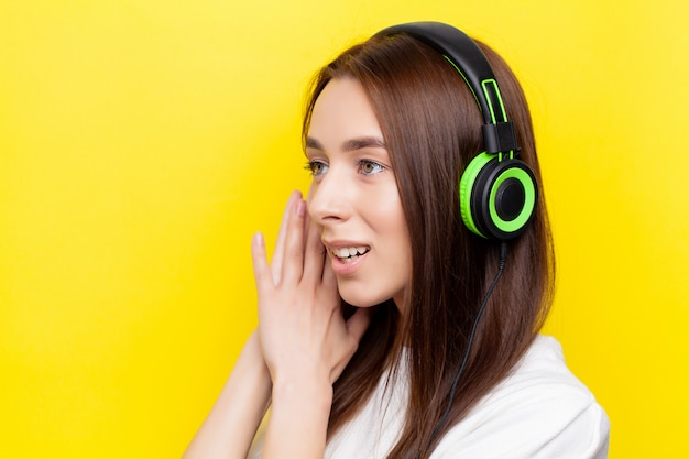 Beautiful young sexy girl dj listening music in green headphones on a yellow
