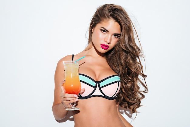 Красивая молодая сексуальная девушка держит коктейль в бикини, изолированном на белом фоне