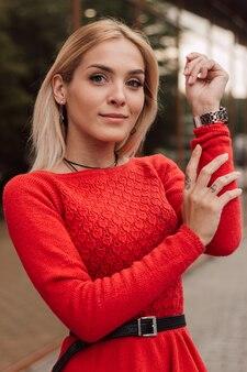 街の路上で赤いドレスを着た美しい若いセクシーな女の子