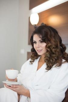 커피 한잔과 함께 집에서 휴식 흰색 목욕 가운에 아름다운 젊은 섹시한 여자