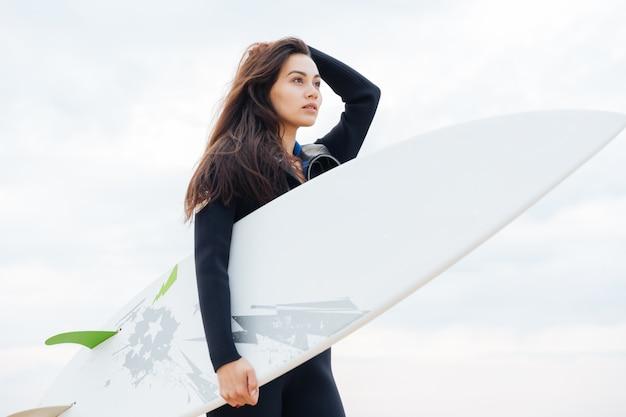 해변에서 산책하는 아름 다운 젊은 섹시 한 서퍼 소녀