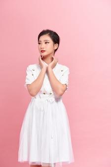 Красивая молодая сексуальная женщина в белом платье позирует у розовой стены