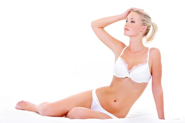 매혹적인 포즈로 침대에 앉아 흰색 란제리에 아름다운 젊은 섹시한 여자