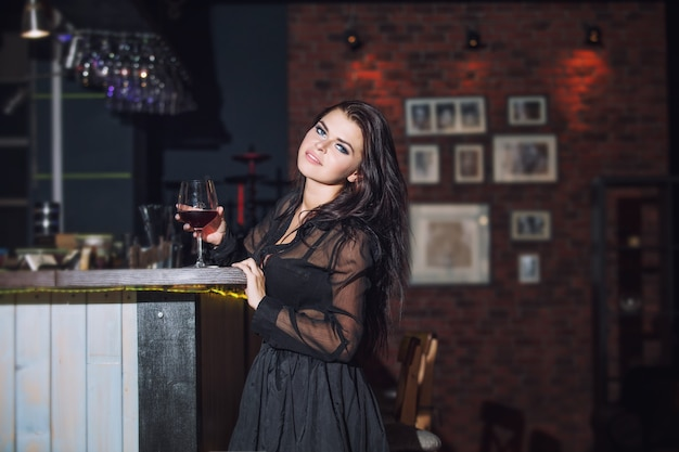 Beautiful young sexy woman model fashionable and luxurious with makeup at the bar with a glass of winan