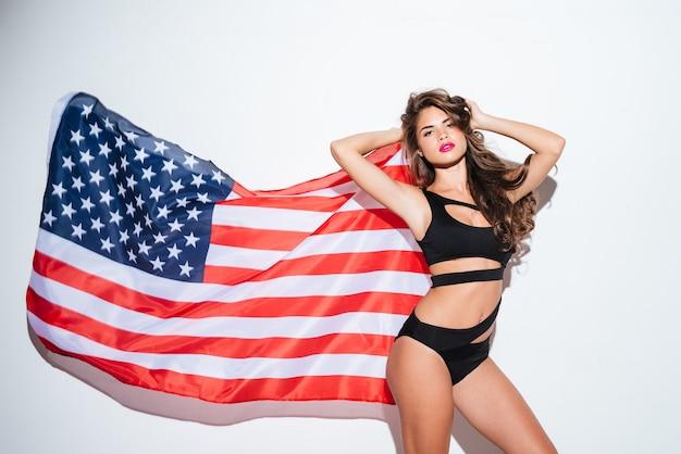 Красивая молодая сексуальная женщина позирует в бикини с американским флагом, изолированным на белом фоне