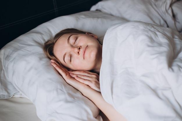 Красивая молодая сексуальная женщина спит в белой спальне с закрытыми глазами утреннее время
