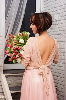 호텔 방에 튤립의 큰 꽃다발과 함께 아름 다운 젊은 섹시 한 여자