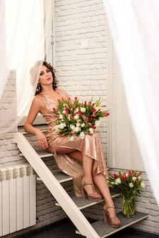 Beautiful young sexy woman with a large bouquet of tulips in a hotel room
