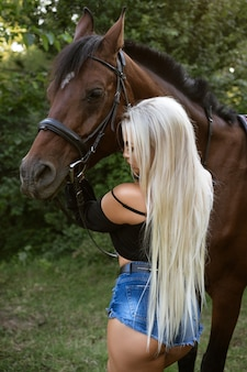 ショートパンツで長い白い髪を持つ美しい若いセクシーな女性は馬と立っています