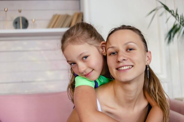 Красивая молодая мама-одиночка со своей очаровательной маленькой дочкой весело играет, улыбаются и обнимаются.