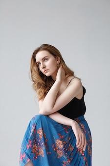 青いスカートの美しい若い座っている女性、かわいい思慮深いモデルの屋内の肖像画。スタジオでポーズをとる自然なきれいな女性