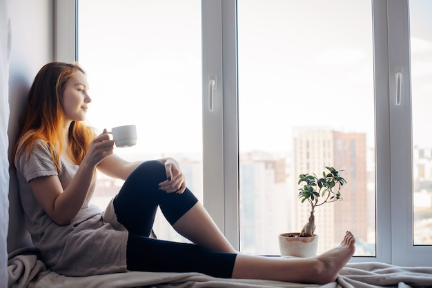 Beautiful young slender girl sitting on the windowsill at home, side view, copy space. outside the window sky and tall city buildings. red-haired woman drinks tea or coffee, looking at the metropolis.