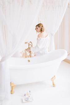 Красивая молодая стройная женщина в рубашке утром в светлой комнате рядом с белой ванной с золотой арматурой.
