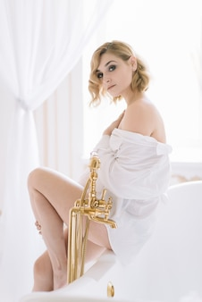 Beautiful young slender woman in a shirt in the morning in a bright room next to a white bath with gold fittings.