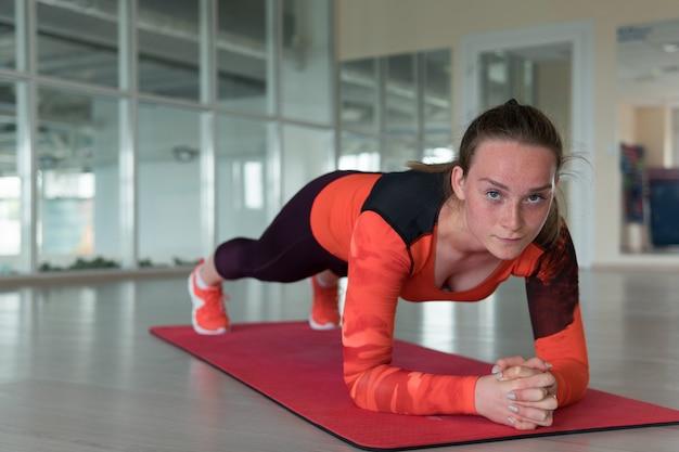 Красивый молодой стройный спортсмен в костюме делает планку для упражнений и смотрит в камеру