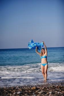 海のビーチで水に立っている美しい若いスリムな女の子。青い水着、ドレス、ショールサロンスカート。七面鳥。休暇。休暇。日光。テキストのための場所