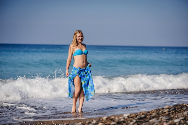 Beautiful young slim girl standing in water at the sea beach. in a blue bathing suit, dress, shawl sarong skirt. turkey. vacation. vacation. sunlight. place for text close up