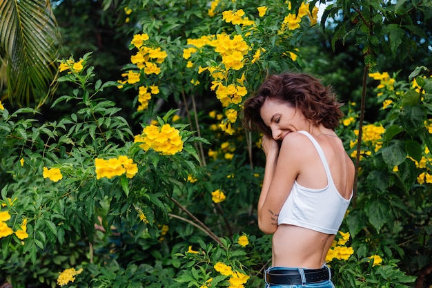 Beautiful young slim stylish fit caucasian happy woman in white crop top and denim pants in park surrounded by yellow thai flowers