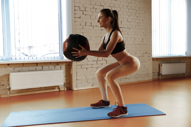 Medballとジムでいくつかの体操をしている美しい若いスリムな女性。アスリート、スポーツ、ロープ、トレーニング、トレーニング、エクササイズ、健康的なライフスタイルの概念