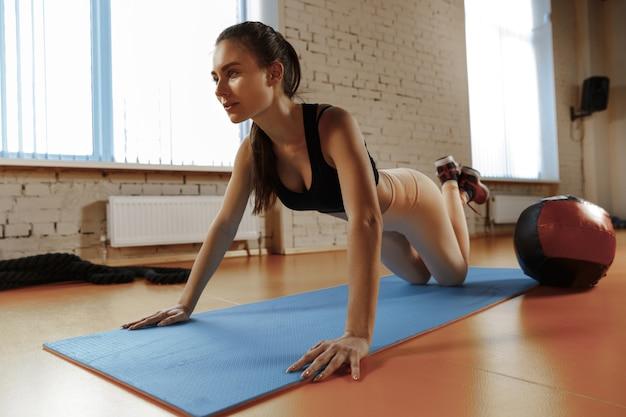 Красивая молодая стройная женщина делает гимнастику в тренажерном зале с медболом.
