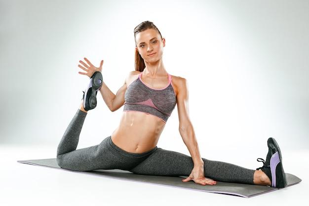 白い背景に対してジムでストレッチ体操をしている美しい若いスリムな女性