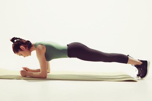 白いスタジオに対してジムでストレッチ体操をしている美しい若いスリムな女性
