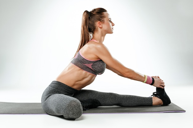 Красивая молодая стройная женщина делает упражнения на растяжку в тренажерном зале против белого