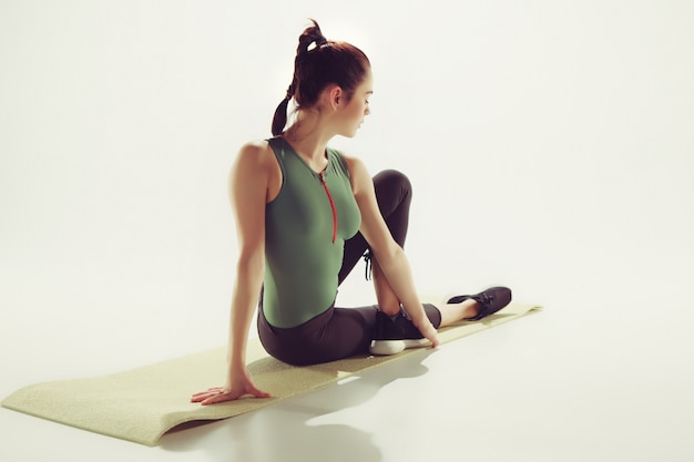 Beautiful young slim woman doing stretching exercises at the gym against white studio