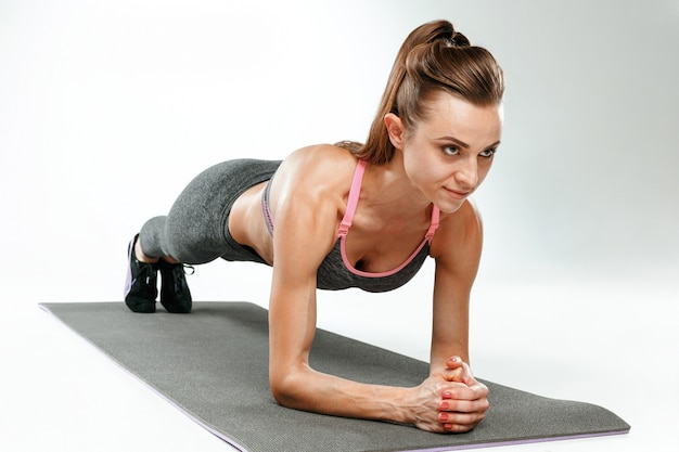 Beautiful young slim woman doing stretching exercises at the gym against white