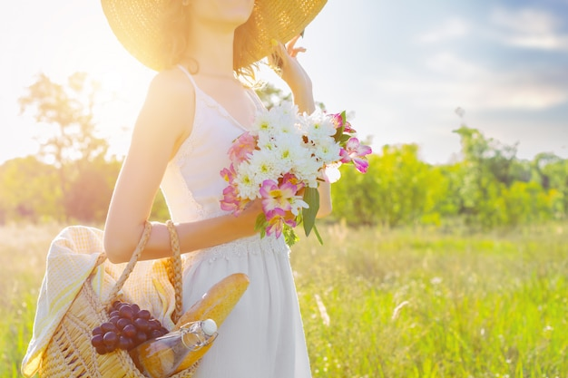 Beautiful young slim woman holding basket with bottle of water, baguette, grape and bouquette of flowers. romantic girl in white dress and fashionable hat is smiling on field at sunset. provence style