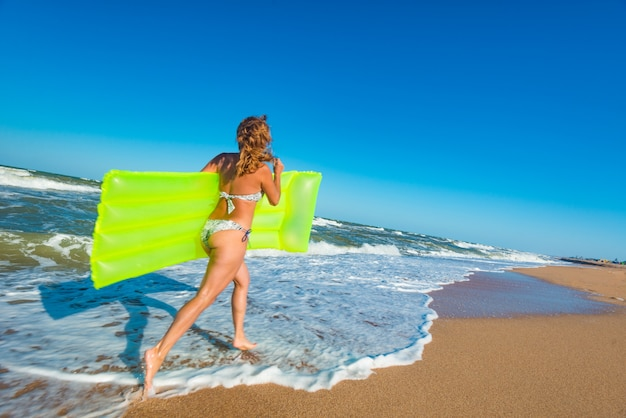 수영복에 아름 다운 젊은 슬림 여자는 화창한 따뜻한 여름 날에 폭풍우 치는 바다 파도 근처 모래 사장을 따라 에어 매트리스와 함께 해변을 따라 실행됩니다. 관광 및 휴가 개념