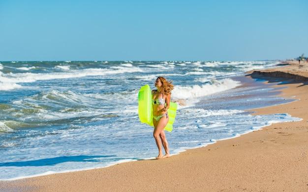 Красивая молодая стройная женщина в купальнике бежит по пляжу с надувным матрасом