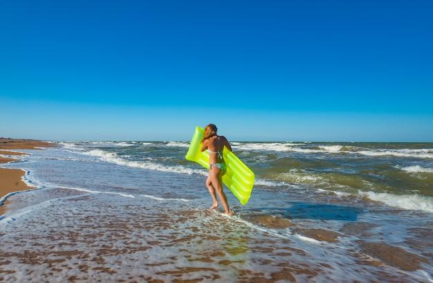 수영복에 아름 다운 젊은 슬림 여자는 에어 매트리스와 함께 해변을 따라 실행