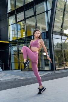 현대 유리 건물, 건강한 생활 방식 근처에서 아침 운동을 하는 sporwear에 있는 아름다운 젊은 날씬한 여성
