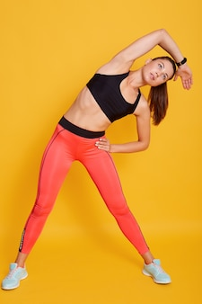 Beautiful young slim woman isolatedover yellow background, doing stretching exercise, female warming up before working out in gym