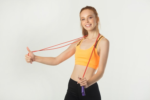 Beautiful young slim woman with red hair in sportswear with a skipping rope in hands