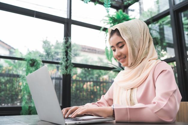 Красивая молодая женщина улыбается азиатских мусульман, работающих на ноутбуке, сидя в гостиной дома