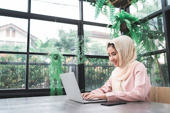 Beautiful young smiling asian muslim woman working on laptop sitting in living room at home