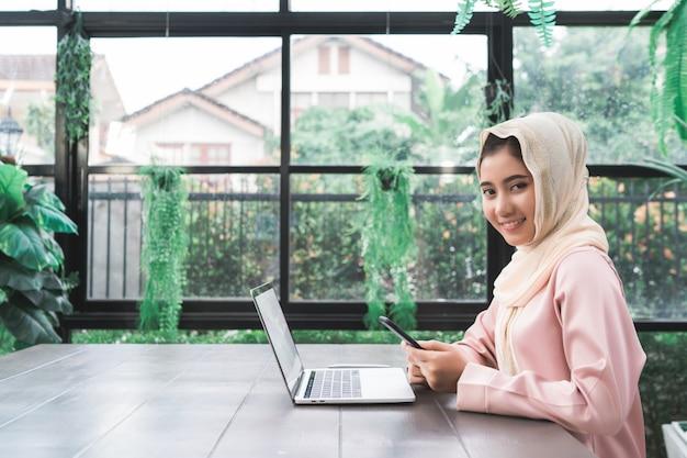 美しい若い笑顔アジアのイスラム教徒の女性は、家庭でリビングルームに座って電話で働く