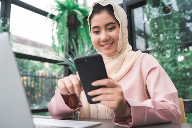 Beautiful young smiling asian muslim woman working on phone sitting in living room at home