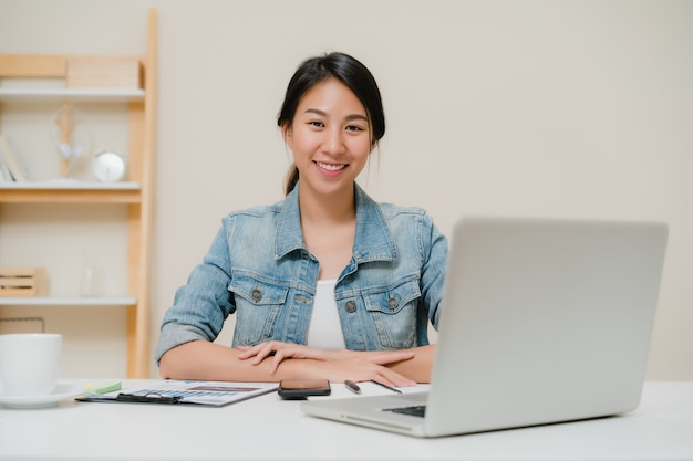 Beautiful young smiling asian woman working laptop on desk in living room at home.