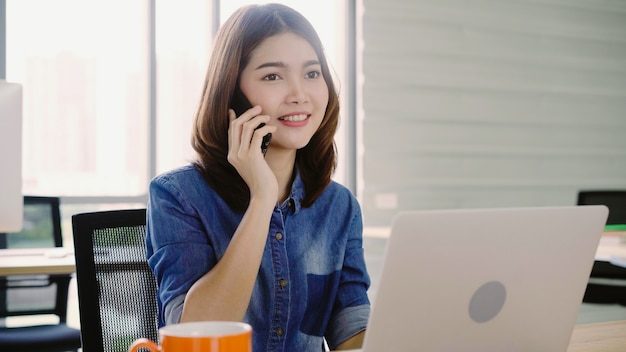 Beautiful young smiling asian woman working on laptop while enjoying using smartphone at office.
