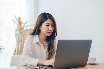 Beautiful young smiling Asian woman working on laptop while at home in office work space