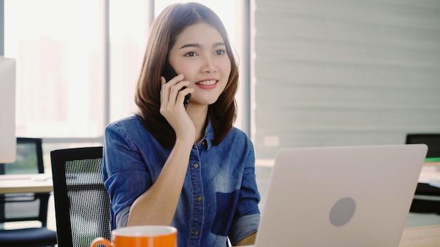 オフィスでスマートフォンを使用して楽しんでいる間ラップトップに取り組んで美しい若い笑顔アジア女性。
