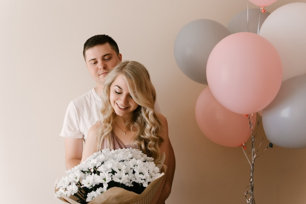 Красивая молодая улыбающаяся блондинка и парень с воздушными шарами и цветами белых ромашек или хризантем
