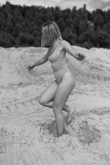 모래 언덕에 포즈를 취하는 아름 다운 젊은 웃는 금발의 여자