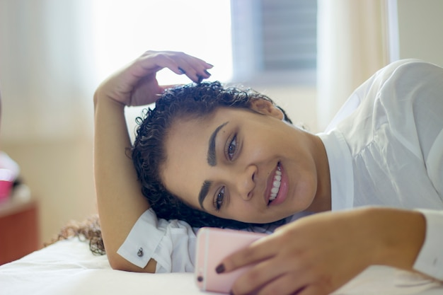 Beautiful young smiling brunette woman lying in white bed and using a phone in her bedroom