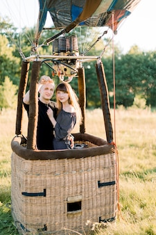Beautiful young smiling couple in love, wearing black casual clothes, staying and hugging in air balloon basket at sunset, ready for their first balloon flight
