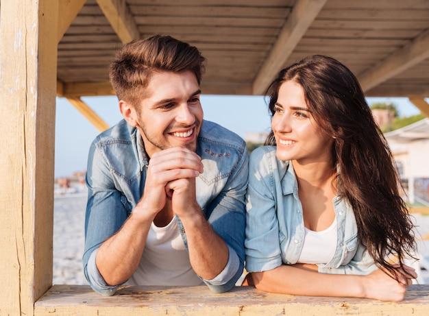Красивая молодая улыбающаяся пара, стоя вместе в пляжном домике